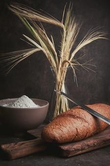 Мука взгляда со стороны в шаре с пшеницей, ножом и хлебом на темном коричневом цвете. вертикальный