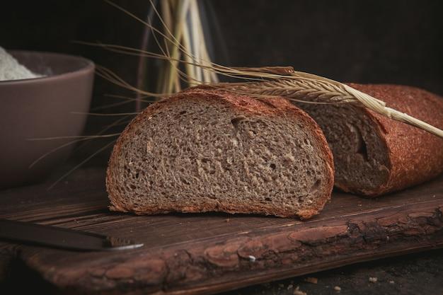 Кусок вид сбоку хлеба на разделочную доску и темно-коричневый.