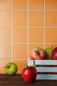 Яблоки в белой деревянной коробке на деревянном и оранжевом фоне плитки. вид сбоку.