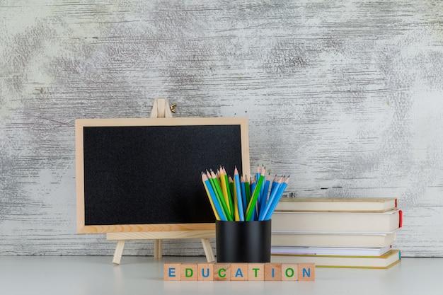 黒板、鉛筆、本、白の木製キューブの教育テキストで学校のコンセプトに戻る