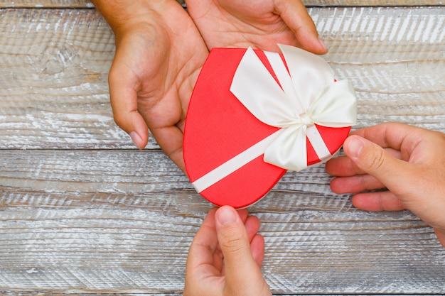 フラット木製の背景に誕生日のコンセプトが横たわっていた。プレゼントボックスを授受する手。