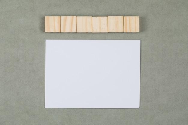 木製キューブ、平らな灰色の背景に白紙のビジネスと金融の概念を置きます。