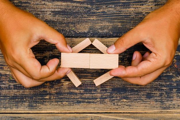 フラット木製の背景のビジネスコンセプトを置きます。木製のブロックをマージする手。