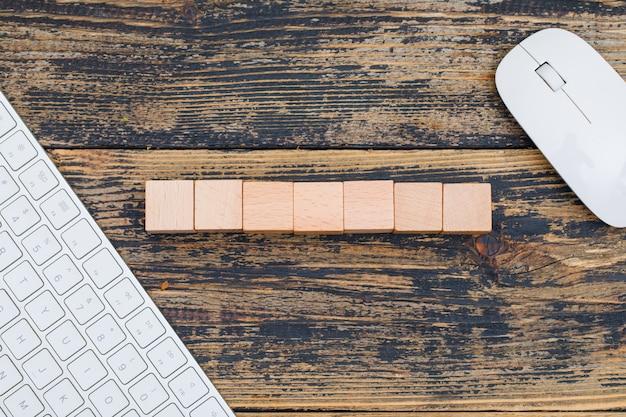 木製キューブ、コンピューターのマウス、木製の背景フラットのキーボードのビジネスコンセプトを置きます。