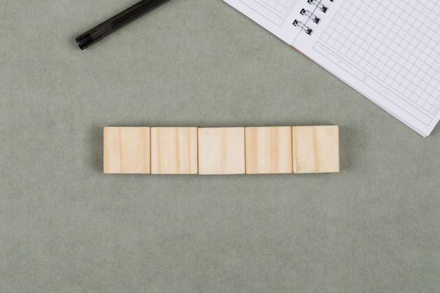木製キューブ、ノートブック、灰色の背景のフラットにペンのビジネスコンセプトを置きます。