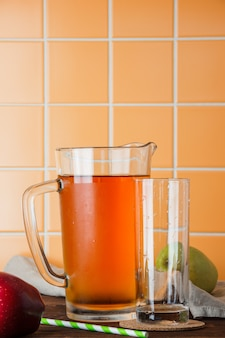 オレンジタイルの背景のテーブルに冷たいリンゴジュース。側面図。テキストのためのスペース
