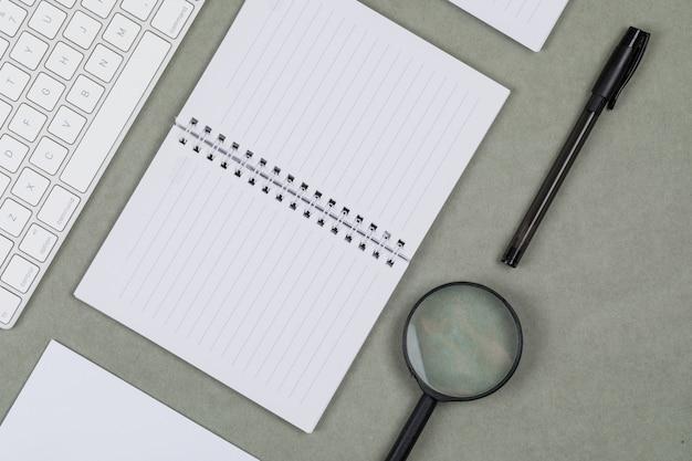 Финансовая концепция с ноутбуками, бумага, ручка, увеличительное стекло, клавиатура на сером фоне плоской планировки.