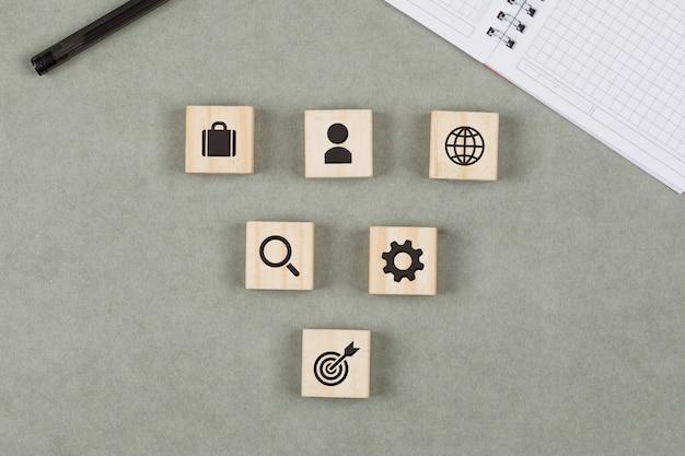 Финансовая концепция с деревянными кубиками, ручка, тетрадь на серой предпосылке кладут квартиру.