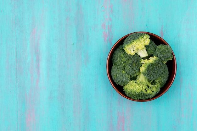 青い木製の表面上のプレートにトップビュー新鮮な緑のブロッコリー