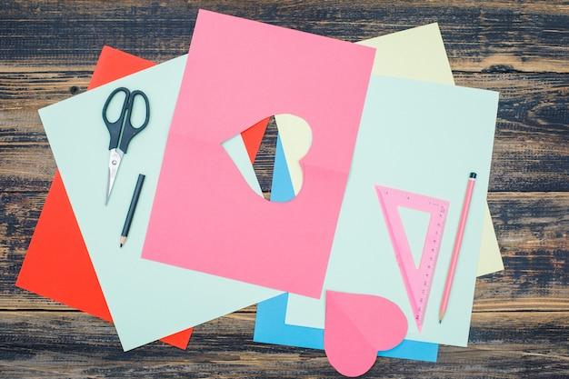 鉛筆、はさみ、定規、平らな木製の背景紙の手作りコンセプト