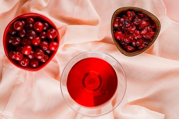 Вишневый сок с вишней, вареньем в бокале на розовом и текстильном