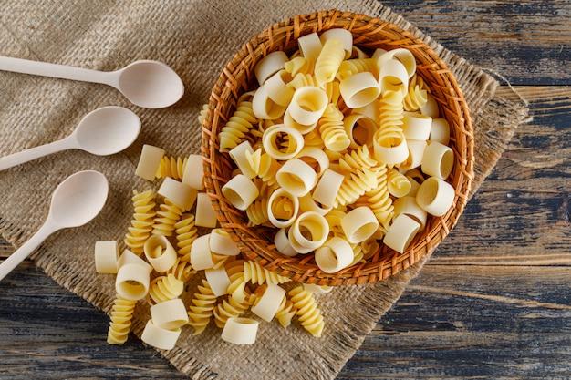 Макаронные макароны в миску с ложками лежат на вретище и деревянный фон