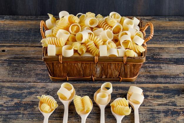Макароны макароны в ложки и корзина высокий угол обзора на деревянном фоне