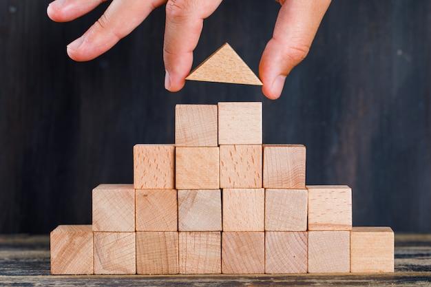 木製と暗い背景の側面図のマーケティングの概念。積み重ねとして木製のブロックを配置する手。