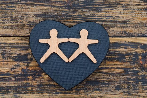 Маркетинговая концепция с деревянными фигурами человека на деревянных и черных сердца фоне плоской планировки.