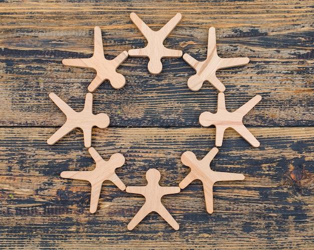 人の木製の数字とマーケティングの概念は、木製の背景フラットにサークルに立つを置きます。