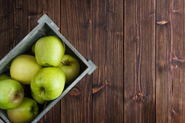 Плоские лежали зеленые яблоки в деревянной коробке на деревянных фоне. горизонтальное свободное пространство для вашего текста