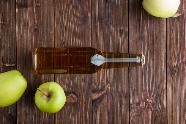 Плоские лежали зеленые яблоки с яблочным соком на деревянных фоне. горизонтальное пространство для текста