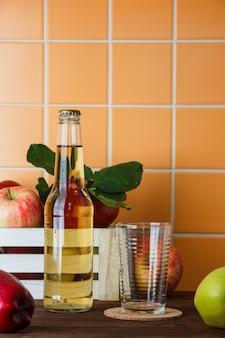 アップルジュースと木製とオレンジ色のタイルの背景のボックスにリンゴのセット。側面図。テキストのためのスペース