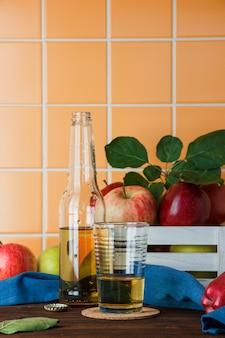 Комплект яблочного сока и яблок в коробке на деревянной и оранжевой предпосылке плитки. вид сбоку. место для текста