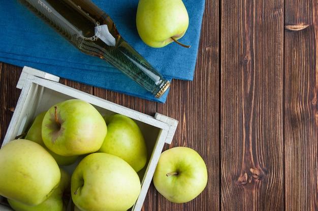 Комплект яблочного сока и зеленых яблок в деревянной коробке на ткани и деревянной предпосылке. плоская планировка место для текста