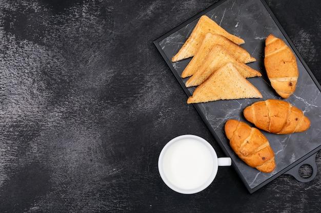 黒の背景にトーストとミルクとコピースペースとクロワッサンの側面図