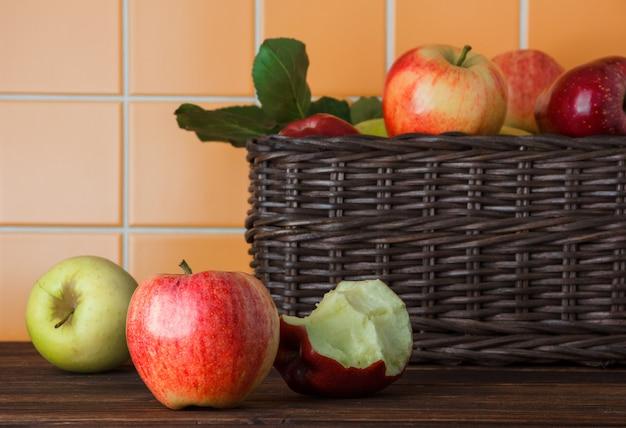 Яблоки взгляда со стороны в корзине с сдержанным одним на деревянной и оранжевой предпосылке плитки. горизонтальный
