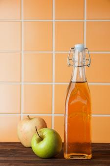 オレンジタイルの背景、側面図のバスケットにリンゴジュースといくつかの新鮮なリンゴ。テキストのためのスペース