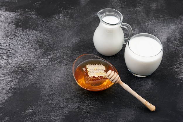 黒い表面の水平に蜂蜜とコピースペースとミルクの側面図