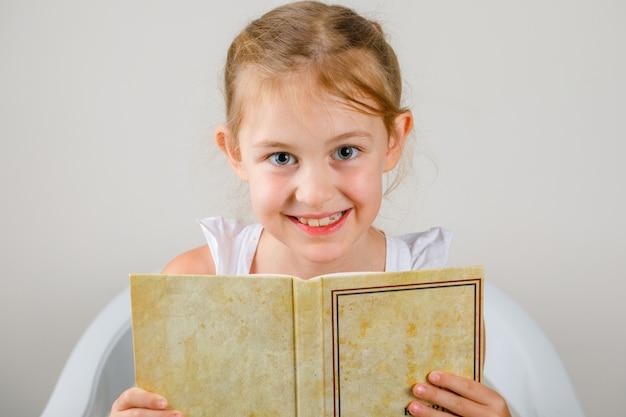 学校のコンセプトに戻る側面図。座っていると本を持っている女の子。