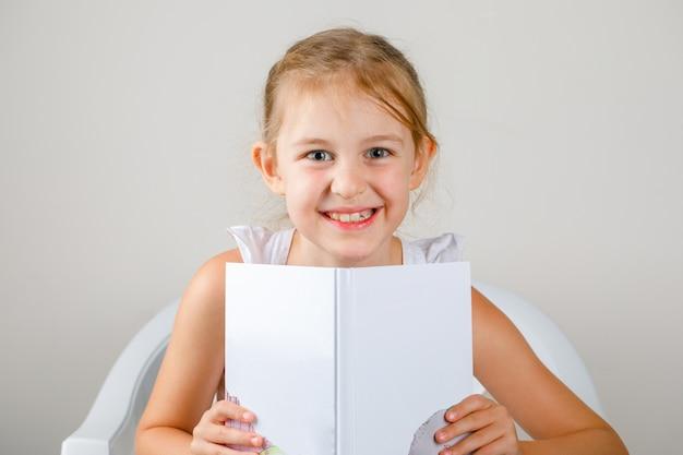 Обратно в школу концепции вид сбоку. маленькая девочка держит книгу.