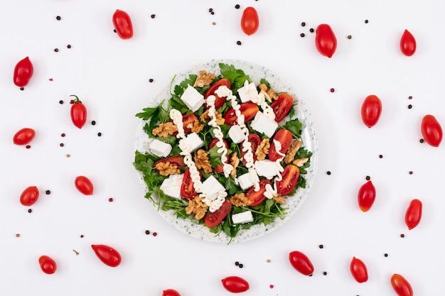 Вкусный овощной салат с майонезом и грецким орехом в окружении красных помидоров черри и молотого перца