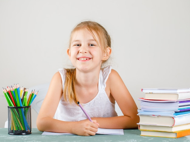 Обратно в школу концепции с карандашами, книги, тетради вид сбоку. маленькая девочка держит карандаш
