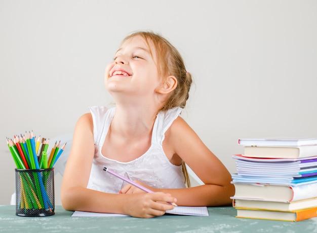 Обратно в школу концепции с карандашами, книги, тетради вид сбоку. маленькая девочка улыбается и держит карандаш.