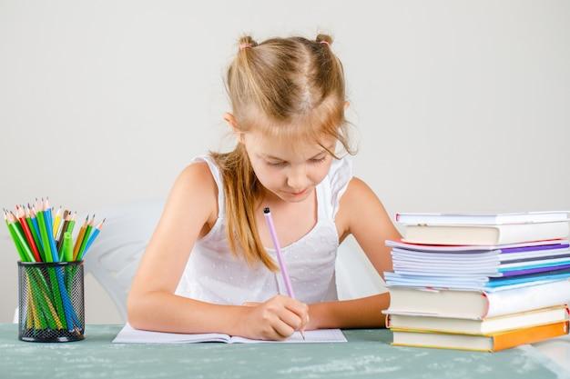 鉛筆で学校のコンセプトに戻って、本の側面図。コピーブックに書いている小さな女の子。