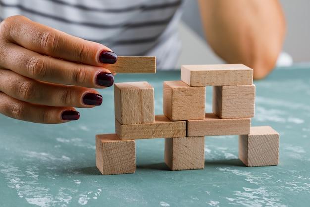 ビジネスコンセプトの側面図です。女性が木製のブロックからタワーを構築します。