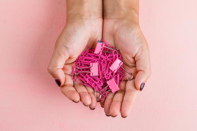 ピンクのテーブルフラットのお祝いのコンセプトが横たわっていた。紙とバインダークリップを保持している女性。