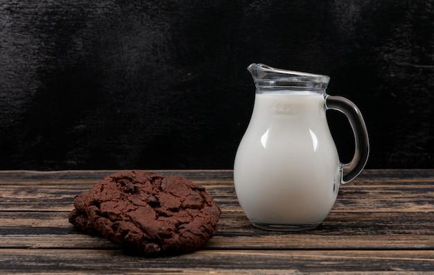 水平の暗い木製のテーブルにミルクとクッキーの水差しの側面図
