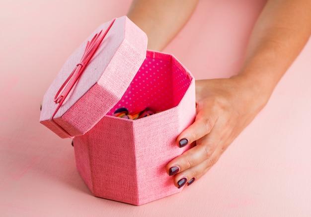 Концепция празднования на розовом столе высокого угла зрения. женщина открытия подарочной коробке.