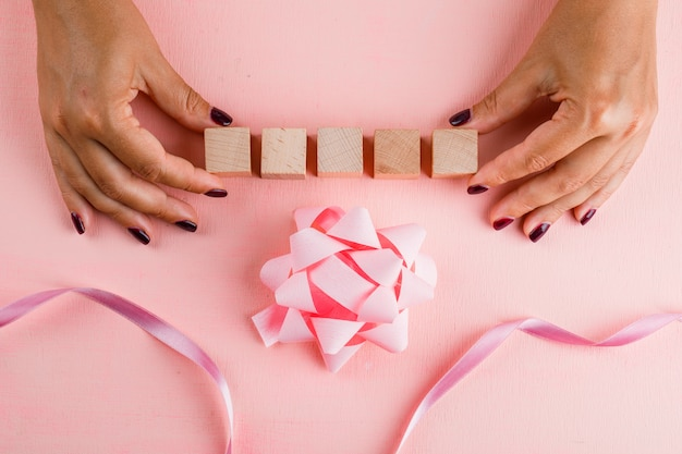 弓でお祝いのコンセプトは、ピンクのテーブルフラットリボンを置きます。木製キューブを保持している女性。