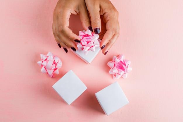 Концепция празднования с лентой луки на розовом столе плоской планировки. женщина готовит подарочные коробки.