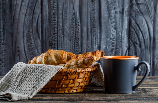 木製のテーブルのお茶側ビューのカップが付いているバスケットのクロワッサン