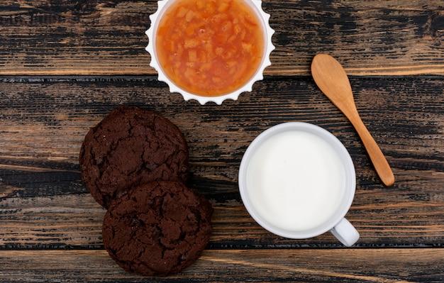暗い木製の表面の水平にミルクとジャムとクッキーのトップビュー