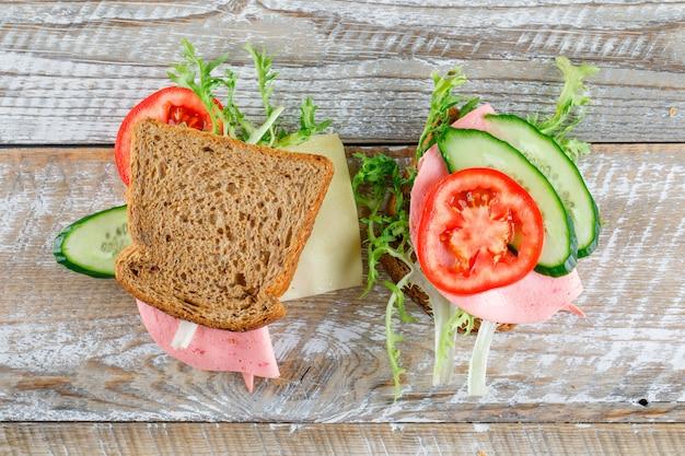 パン、チーズ、トマト、キュウリ、ソーセージ、グリーンサンドイッチのサンドイッチは、木製のテーブルの上に置く