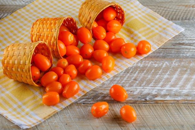 ピクニック布と木製のテーブルに籐のバスケットからの散乱トマト。ハイアングル。