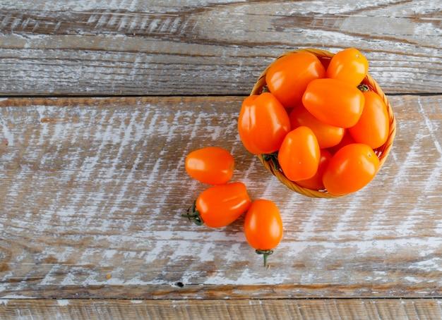 木製のテーブルのバスケットのトマト。フラット横たわっていた。