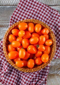 木製とピクニック布の上のバスケットのトマト。フラット横たわっていた。
