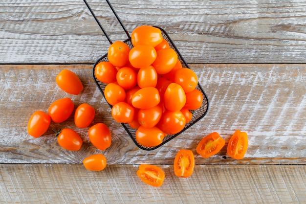ザルフラットトマトを木製のテーブルの上に置く