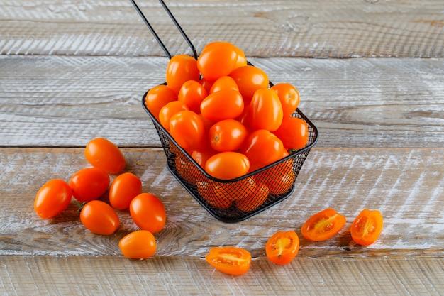 木製のテーブルにザルハイアングルでトマト