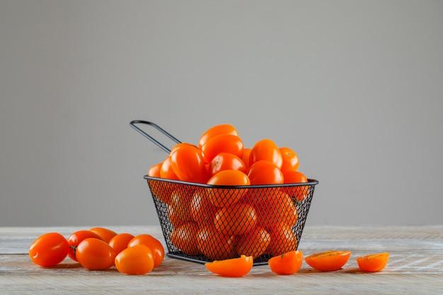木製と灰色のテーブルにザルでトマト。側面図。